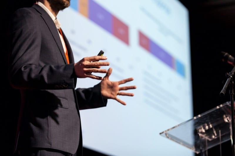 Techniczna obsługa eventów i konferencji - prezenter stoi przy mównicy